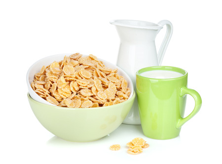 Fresh corn flakes in bowl, milk jug and cup. Isolated on white  photo