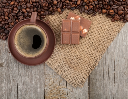 Coffee cup and chocolate on wooden table texture with copy space. View from above photo