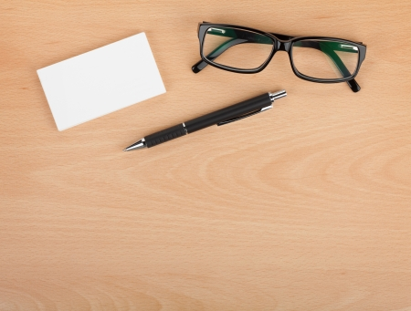 Blank business cards with pen and glasses on wooden office table with copy space photo