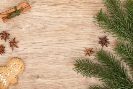 Christmas fir tree, gingerbread cookie and spices on wooden table photo
