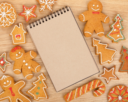 Blank notepad with christmas gingerbread cookies on wooden table photo