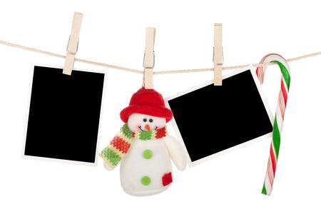 Blanco fotolijsten en sneeuwpop opknoping op de waslijn Geïsoleerd op witte achtergrond Stockfoto