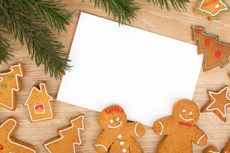 Christmas fir tree, gingerbread cookies and card for copy space on wooden table Stock Photo
