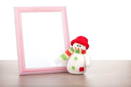 Blank photo frame and christmas snowman on wooden table. Isolated on white background photo