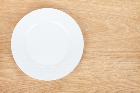 empty plate: Empty white plate on wooden table. View from above