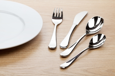 Empty white plate with silverware on wooden table photo