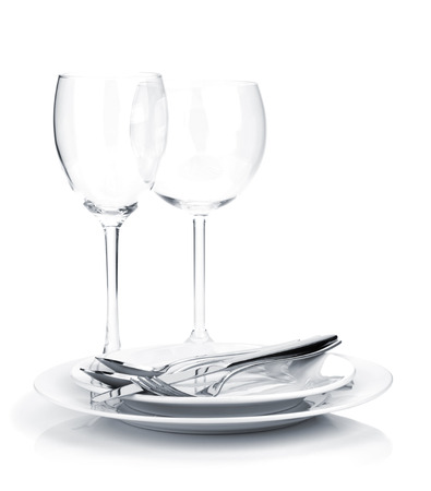 Silverware or flatware on plates and wine glasses.