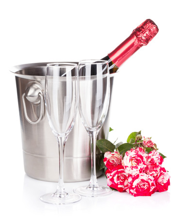 Champagne bottle, two glasses and red rose flowers. Isolated on white background photo