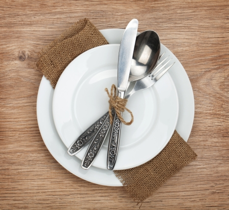 Empty plate and silverware set on wooden table photo