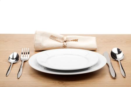 Lege plaat en zilverwerk ingesteld op houten tafel
