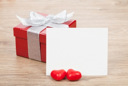 Blank valentines greeting card and small red gift box on wooden table photo