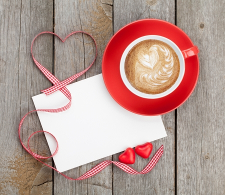 Blank valentines greeting card and red coffee cup on wooden background photo