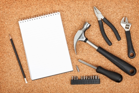 Set of tools on cork panel with notepad for copy space photo