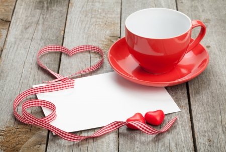 Blank valentines greeting card and red coffee cup on wooden  photo
