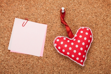 Blank note with toy heart on wooden cork board photo
