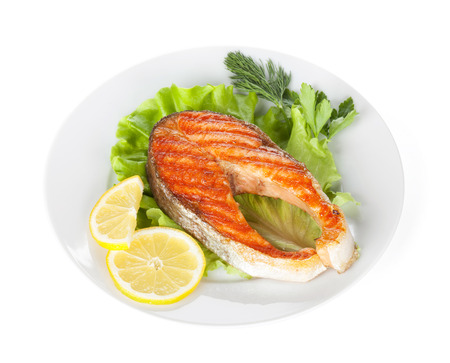 Grilled salmon with lemon slices and herbs on plate. Isolated on white  photo