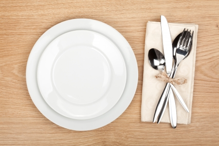 dinner plate: Empty plate and silverware set on wooden table