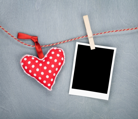 Blank instant and red heart hanging.  photo