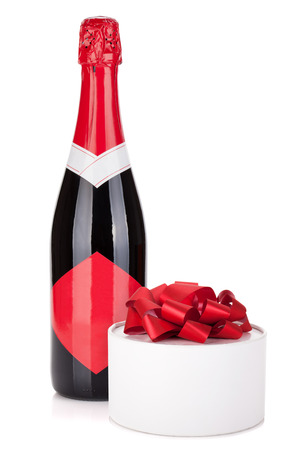 Champagne bottle and gift. Isolated on white background photo