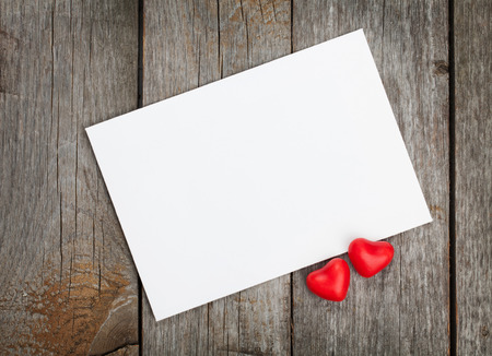 Valentines day blank gift card and red candy hearts on wooden background photo