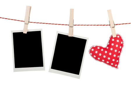 Blank instant photos and red heart hanging. Isolated on white background photo