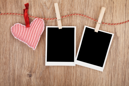 Blank instant photos and red heart hanging. On wooden background photo