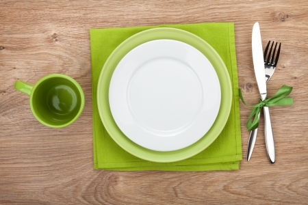 dining set: Fork with knife, blank plates, empty cup and napkin. On wooden table background Stock Photo