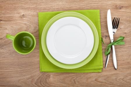 místo: Vidlice s nožem, prázdné talíře, prázdný šálek a ubrousek. Na dřevěném stole pozadí