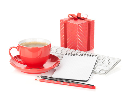 Coffee cup, red gift box and office supplies. Isolated on white background photo