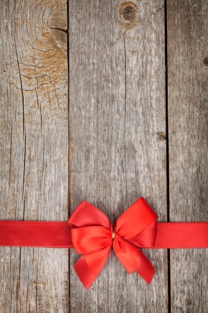 Wooden background with red bow and ribbon with copy space photo