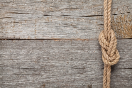 Ship rope knot on old wooden texture background photo
