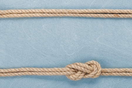 Ship rope knot on blue wooden texture background photo