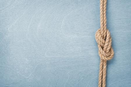 青い木製テクスチャ背景にロープの結び目を出荷します。 写真素材