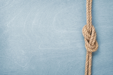 Ship rope knot on blue wooden texture background Stock fotó