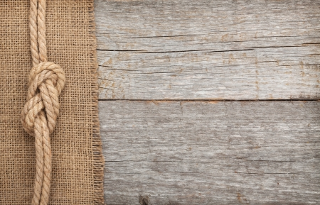 Ship rope on old wood and burlap texture background with copy space Stock Photo - 25357572