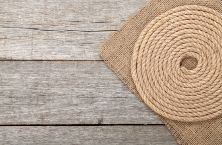 Ship rope on wood and burlap texture background photo