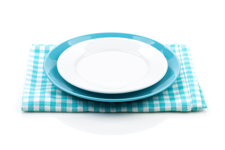 Empty plates over kitchen towel. Isolated on white background Stock Photo