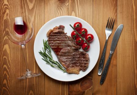 サーロイン ステーキ ローズマリーとチェリー トマトをワインと皿。上からの眺め