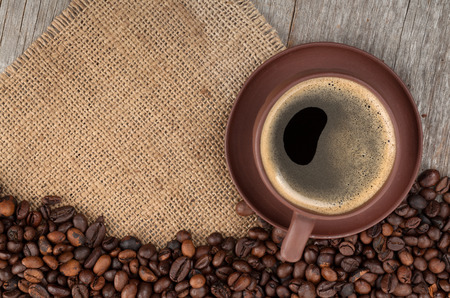 Coffee cup and beans on wooden table background with copy space photo