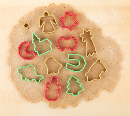 Gingerbread dough for christmas cookies with colorful cookie cutters photo