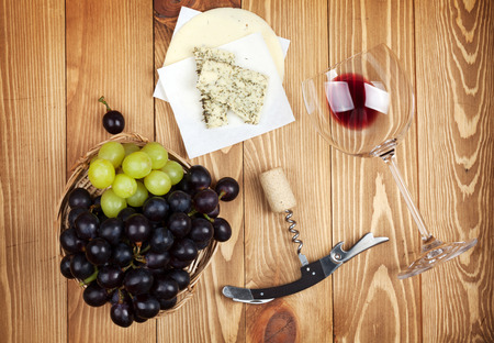 Red wine, cheese and grape on wooden table background photo
