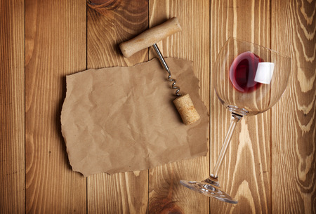 closed corks: Red wine glass, corkscrew and paper for your note on wooden table background