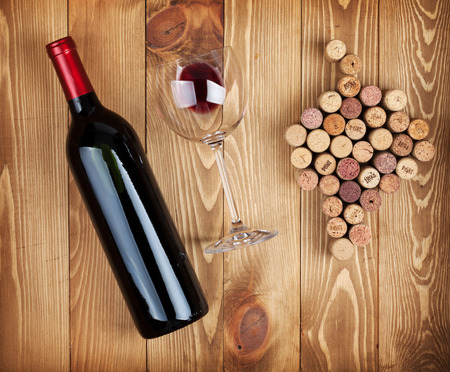 Red wine bottle, glass and grape shaped corks on wooden table background photo