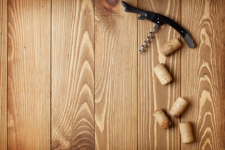 Corkscrew and wine corks on wooden table background with copy space