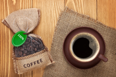 Coffee cup and small bag with beans on wooden table photo