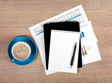 Blank notepad and coffee cup on office wooden table photo