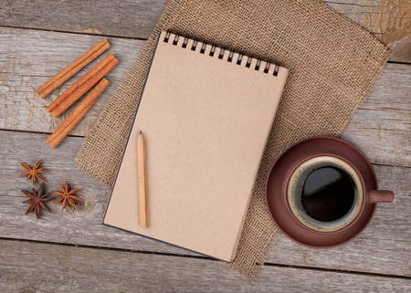 Blank notepad for copy space with coffee cup and spices on wooden table photo