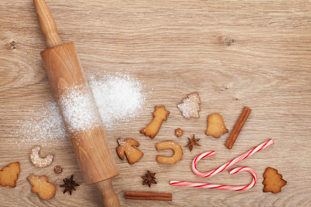 Rolling pin with flour, spices and cookies on wooden table. View from above photo