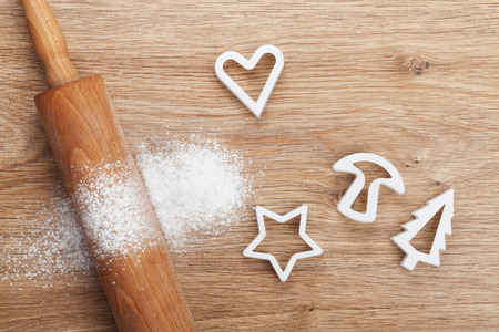 kitchen table top: Rolling pin with flour and cookie cutters on wooden table. View from above Stock Photo