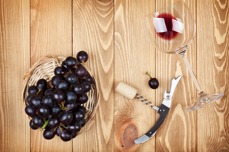 closed corks: Red wine glass, corkscrew and grape on wooden table background Stock Photo